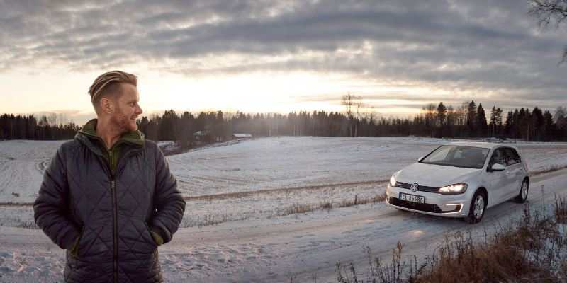Ginge is on a dirt road, in the background stands his e-Golf