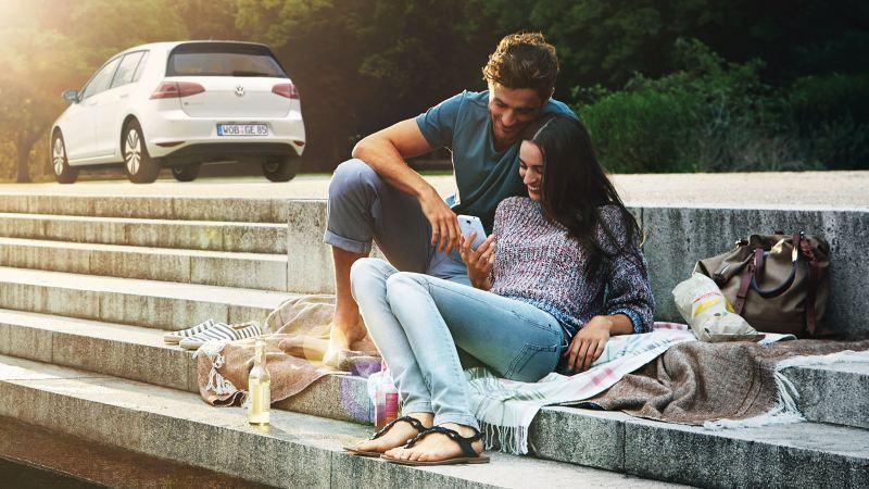 Un couple assis sur des marches regarde un smartphone, leur Volkswagen en arrière-plan