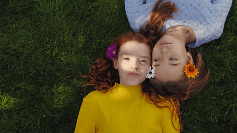 Two girls laying on grass head to head