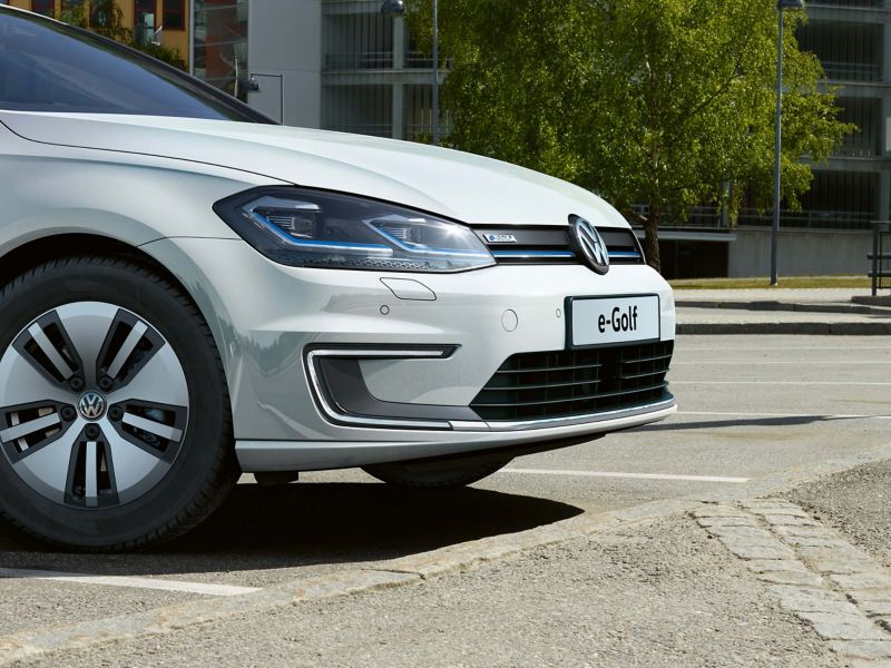 A white Volkswagen e-Golf, charging at an external charge point, in a car park.