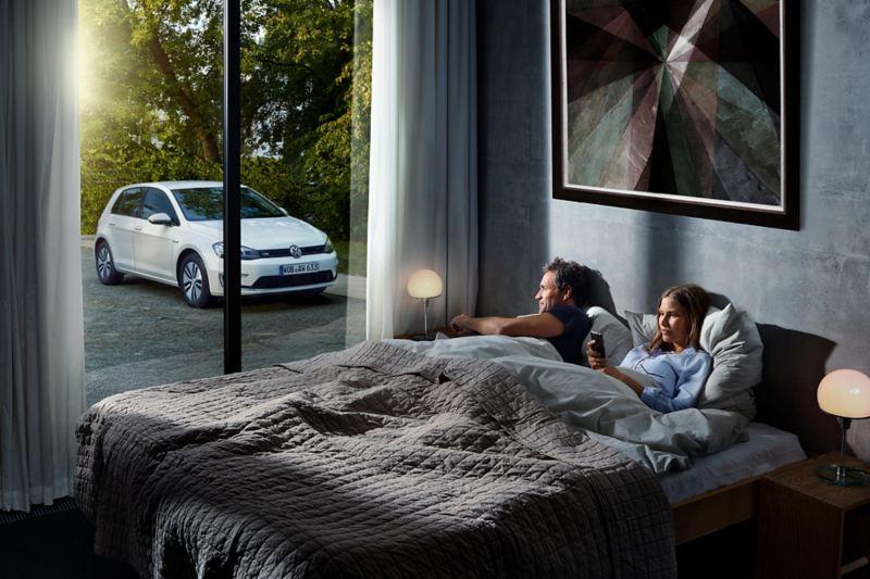 Ett par ligger i sängen med sina smartphones, hanterande en uppdatering till sin bil genom OTA-teknik.