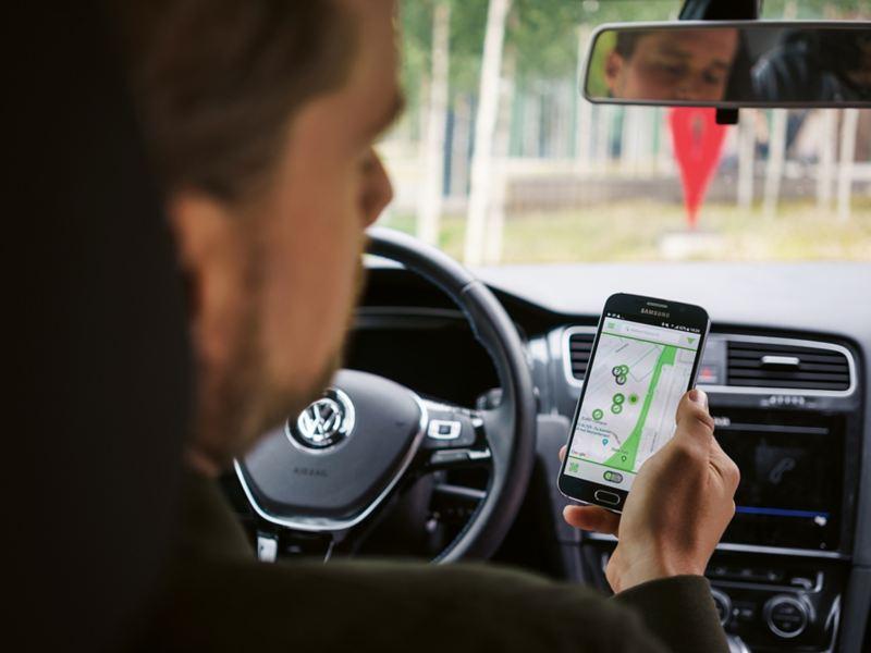 Im Auto mit ausgeschaltetem Motor blickt ein Mann auf sein Smartphone.