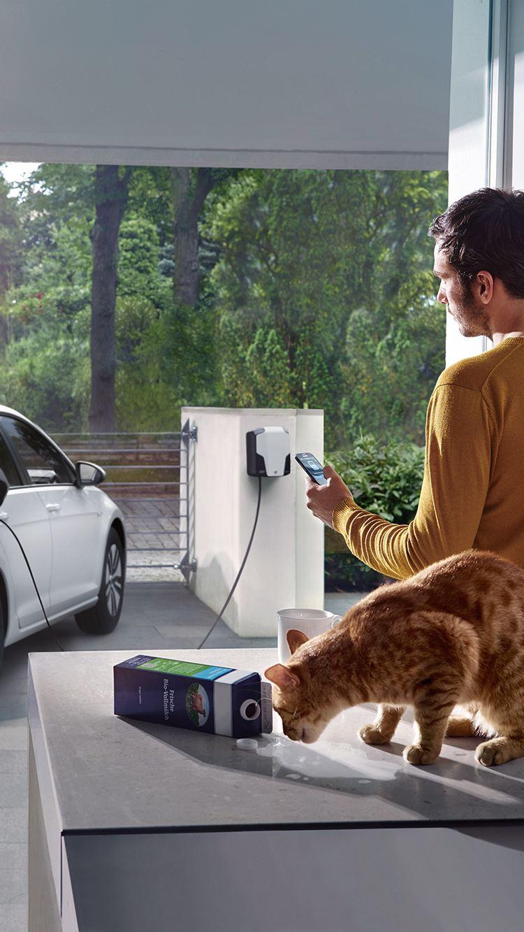 En man använder sin smartphone för att uppdatera sin Volkswagen e-Golf med OTA-teknik