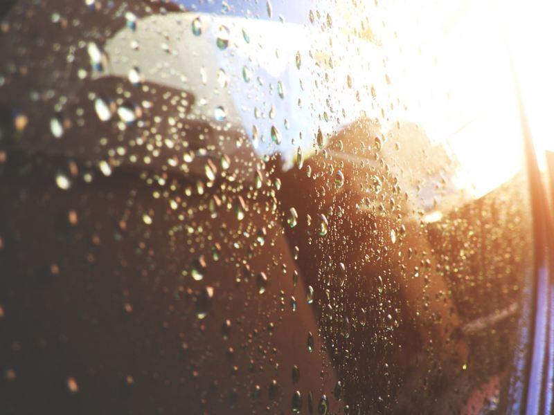 Primo piano del finestrino di un'auto con gocce di pioggia