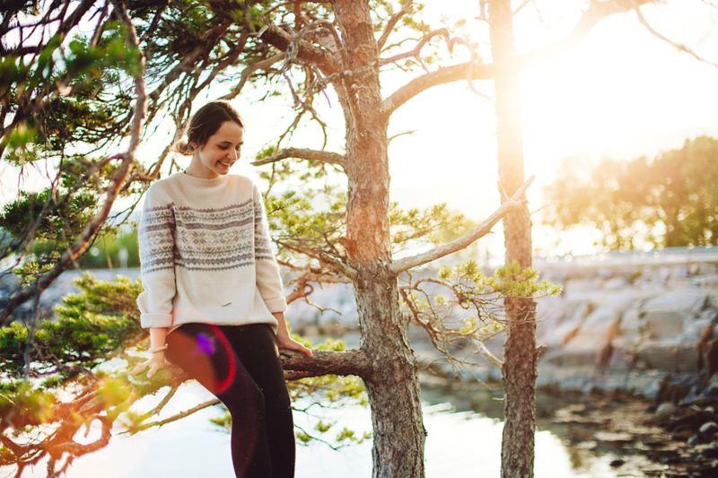 Eine Frau sitzt auf einem Baum.