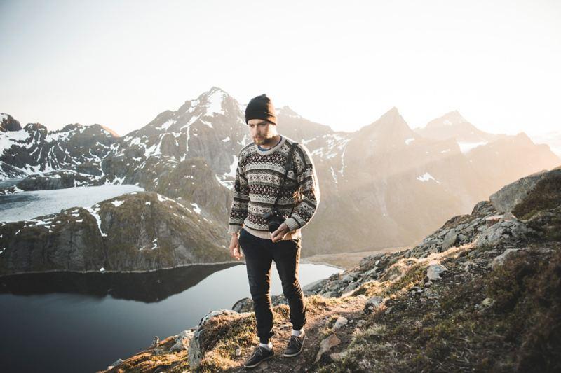 Uomo con maglione tipico norvegese e sullo sfondo una catena montuosa