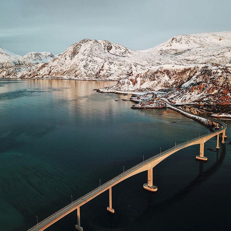 Brücke über einen Fjord in Norwegen vor einer verschneiten Gebirgslandschaft.
