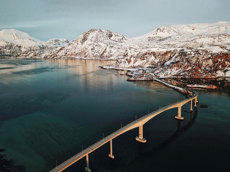 Ponte su un fiordo norvegese e sullo sfondo un paesaggio montano innevato
