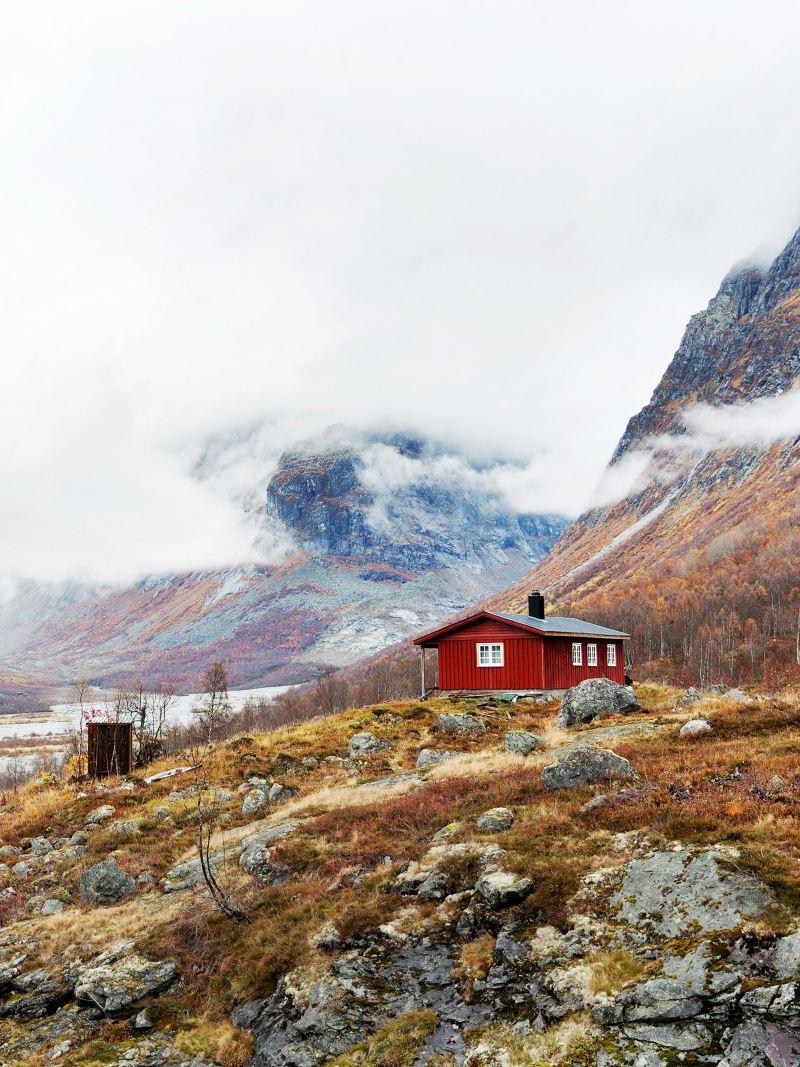 Rote Hütte in einer kargen Gebirgslandschaft.