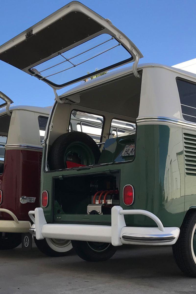 Drei VW Retro-Bullis mit Elektromotor stehen mit offenem Kofferraum nebeneinander.