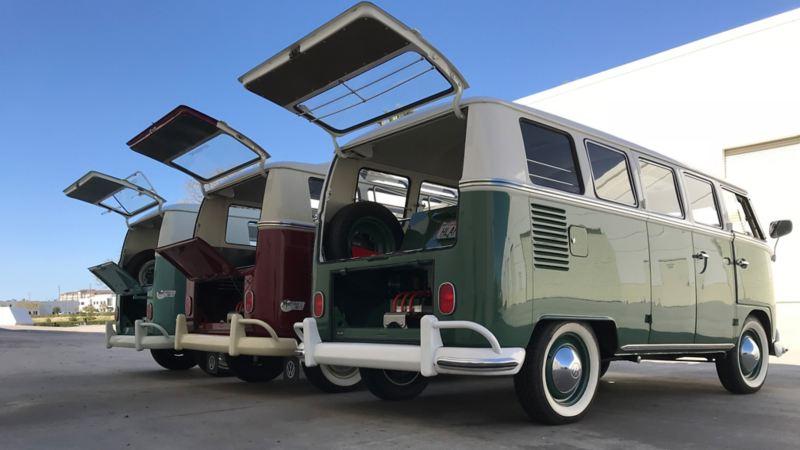Tre Volkswagen Bulli vintage con motore elettrico, parcheggiati uno accanto all'altro, con il bagagliaio aperto