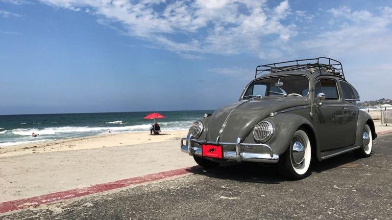 Oldtimer-VW-Käfer steht am Strand.