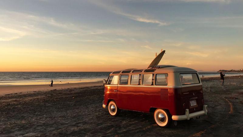 Retro-Bulli mit Elektromotor steht im Sonnenuntergang am Strand.