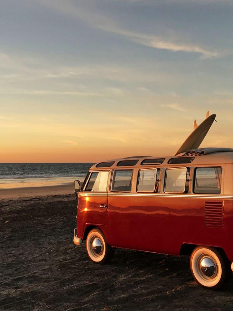 Un Bulli vintage con motore elettrico sulla spiaggia al tramonto