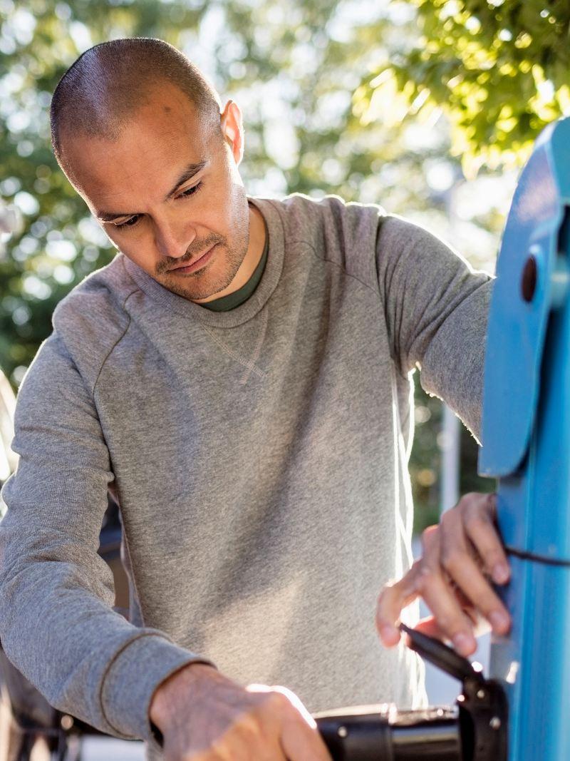 Ein Mann steckt ein Ladekabel in eine Stromtankstelle