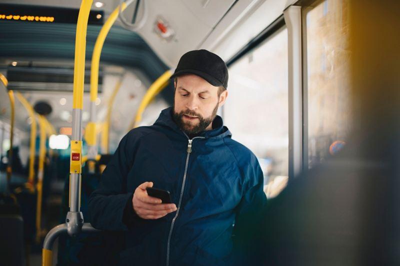 Man steht im Bus und schaut auf sein Handy.