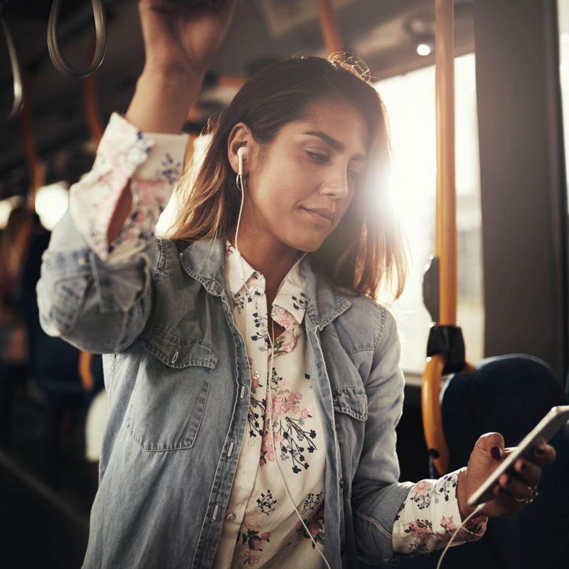 Eine Frau steht im Bus und blickt auf ihr Smartphone.