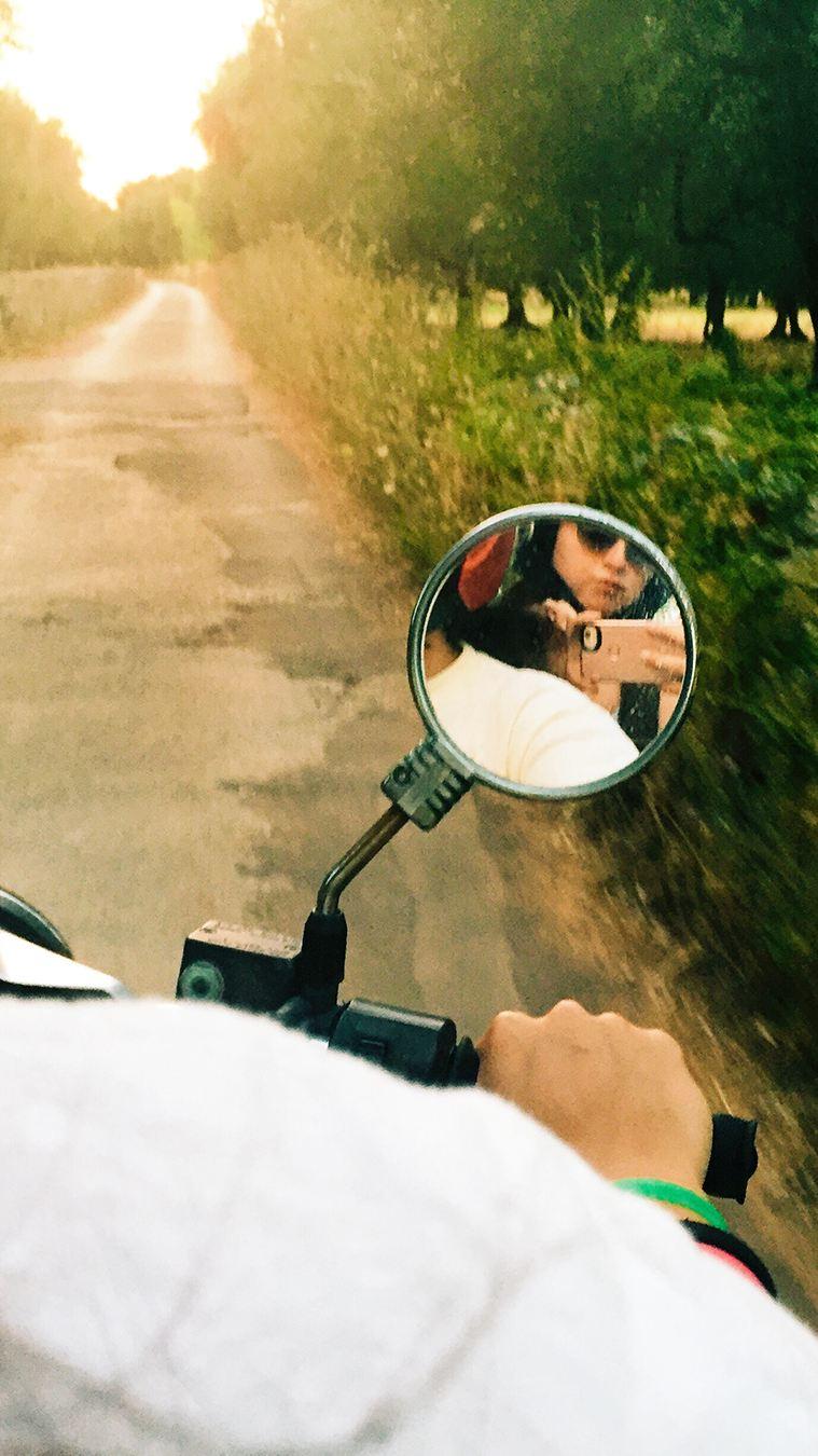Coppia di ragazzi riflessa nello specchietto di uno scooter