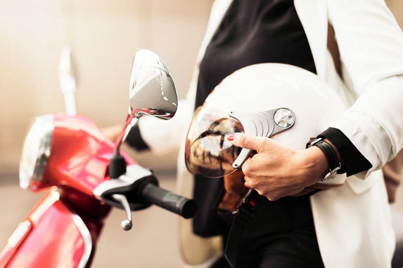 Ragazza vicino ad uno scooter con casco in mano