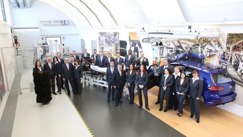 Eine Besuchergruppe posiert vor einem Montageband für ein Gruppenfoto