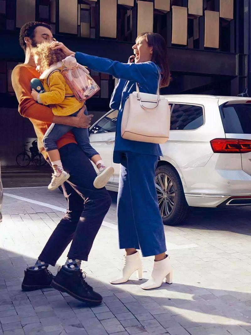 Deux Passat SW vues arrière garées dans un parking exterieur, couple avec un enfant
