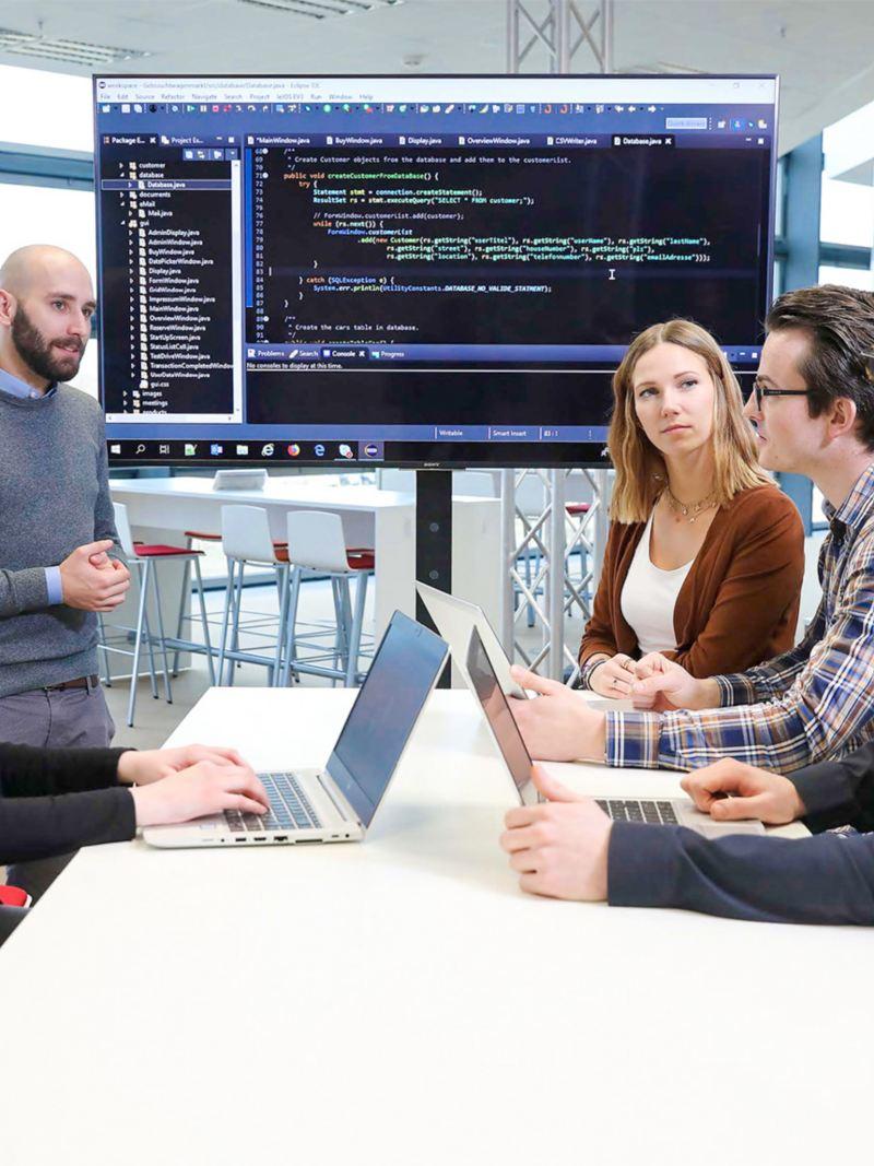 Zwei Frauen und drei Männer in einem Meeting vor einem großen Monitor