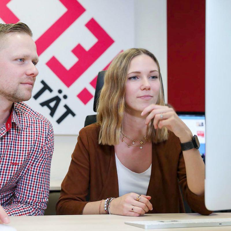 Eine Frau und ein Mann schauen zusammen auf einen Computer