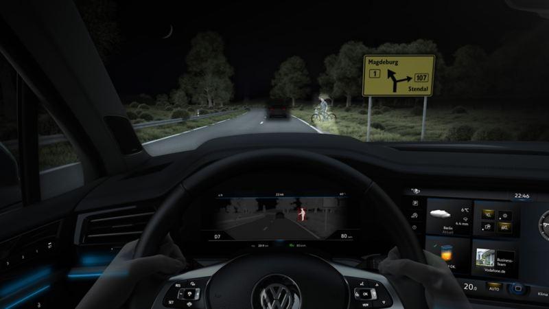Vista attraverso il parabrezza di una Volkswagen, la strada viene illuminata dai fari