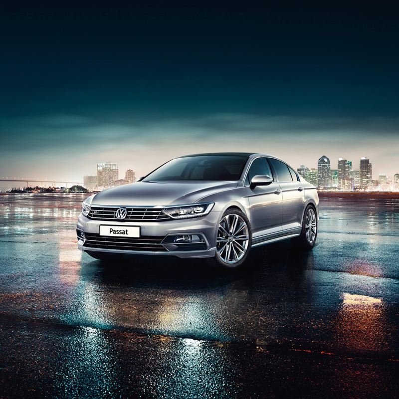 Silver Volkswagen Passat, with a city backdrop at night