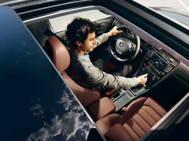 Vue d'un homme dans sa Volkswagen, part le toit ouvrant