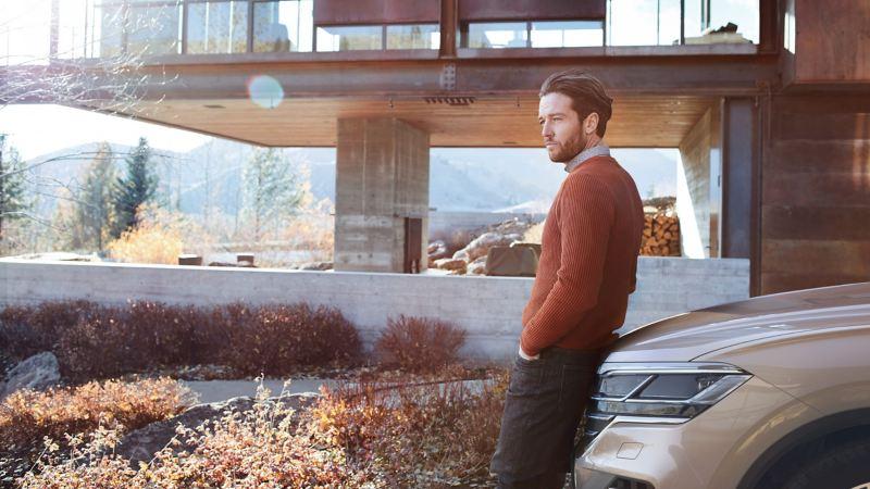 Ein Mann lehnt an die Motorhaube eine VW Touareg