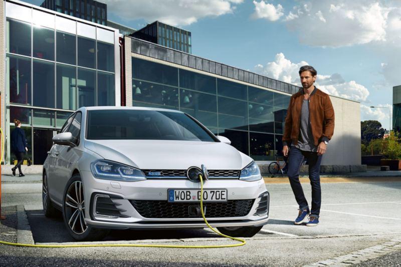 VW Golf GTE von vorne, Ladekabel ist am VW Logo angeschlossen