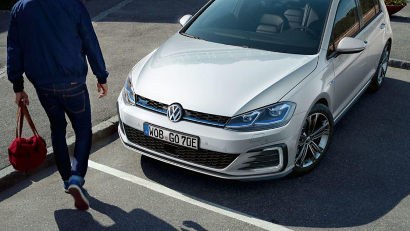 VW Golf GTE parking on a road, man walking by