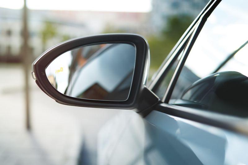 Rétroviseur extérieur d'une VW Golf avec symbole du Blind Spot Sensor visible.