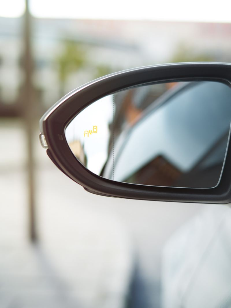 VW Golf side mirror with symbol of the Blind Spot Sensor visible