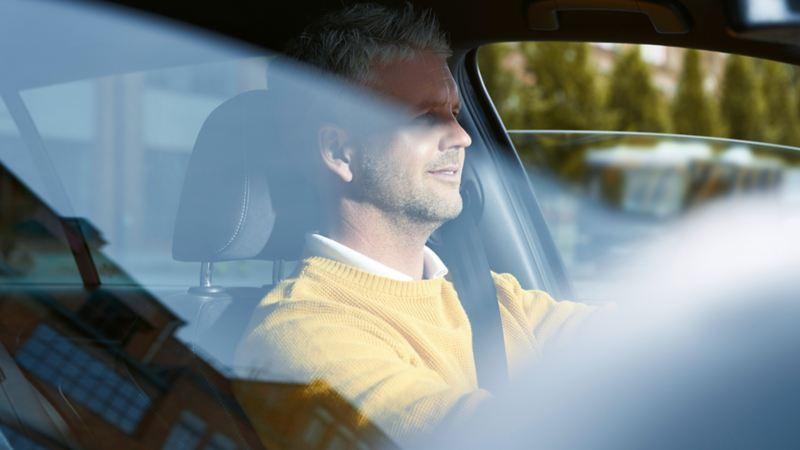 Uomo con pullover giallo alla guida di una Volkswagen