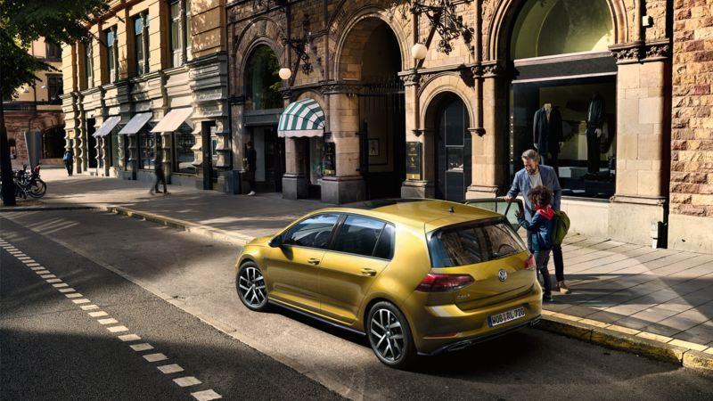 Ein VW Golf 7 parkt an einer Straße, ein Mann und ein Junge öffnen eine hintere Tür.