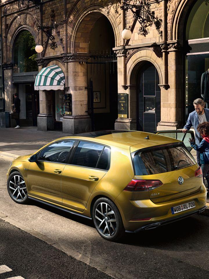 VW Golf in Gelb am Straßenrand. Ein Vater öffnet seinem Kind die Tür zum Einsteigen.