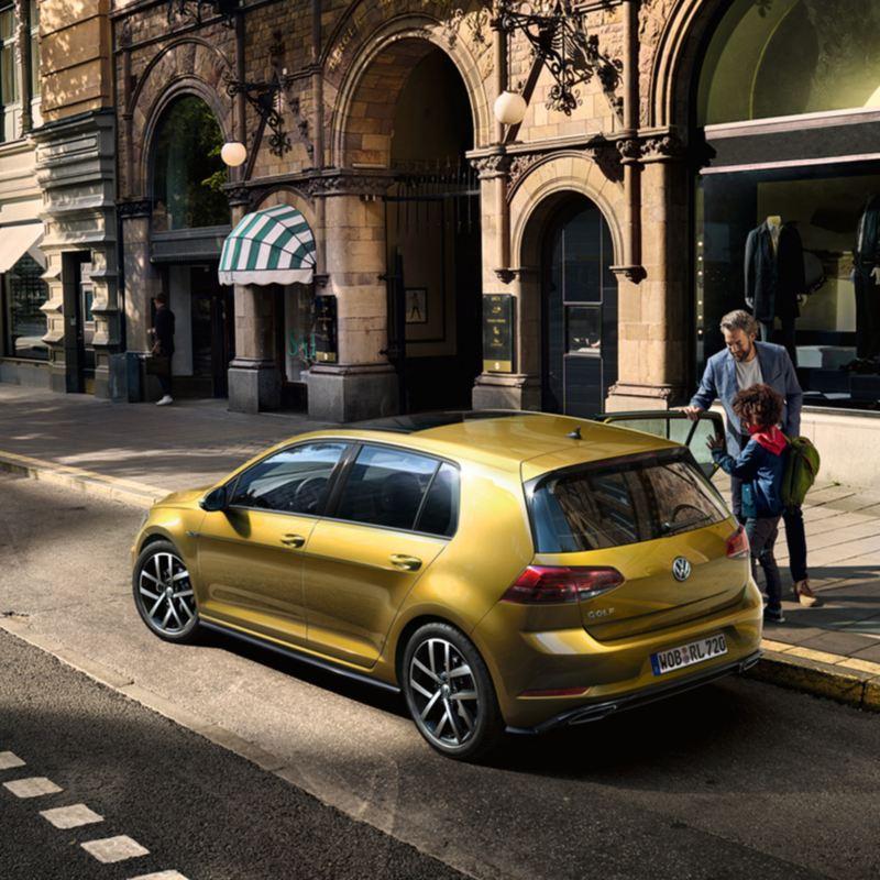 Mann und Kind stehen an geöffneter Tür eines VW Golf auf der Beifahrerseite