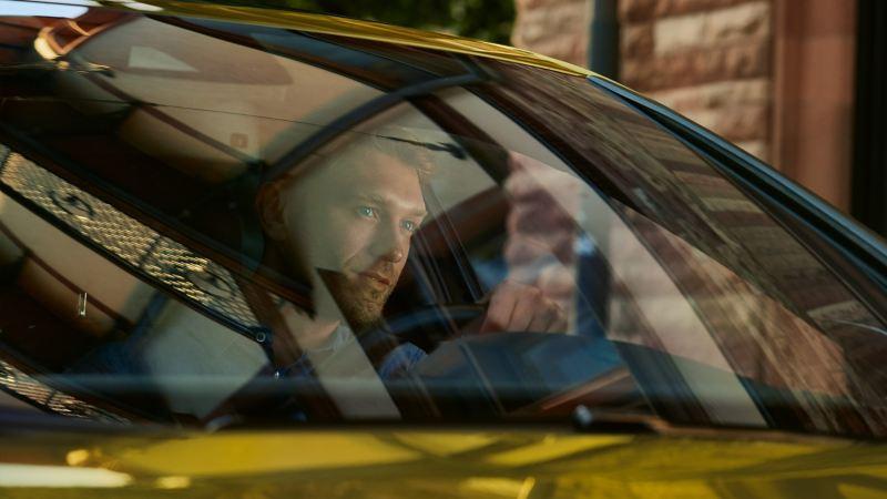 Man tittar ut från vindrutan på sin VW