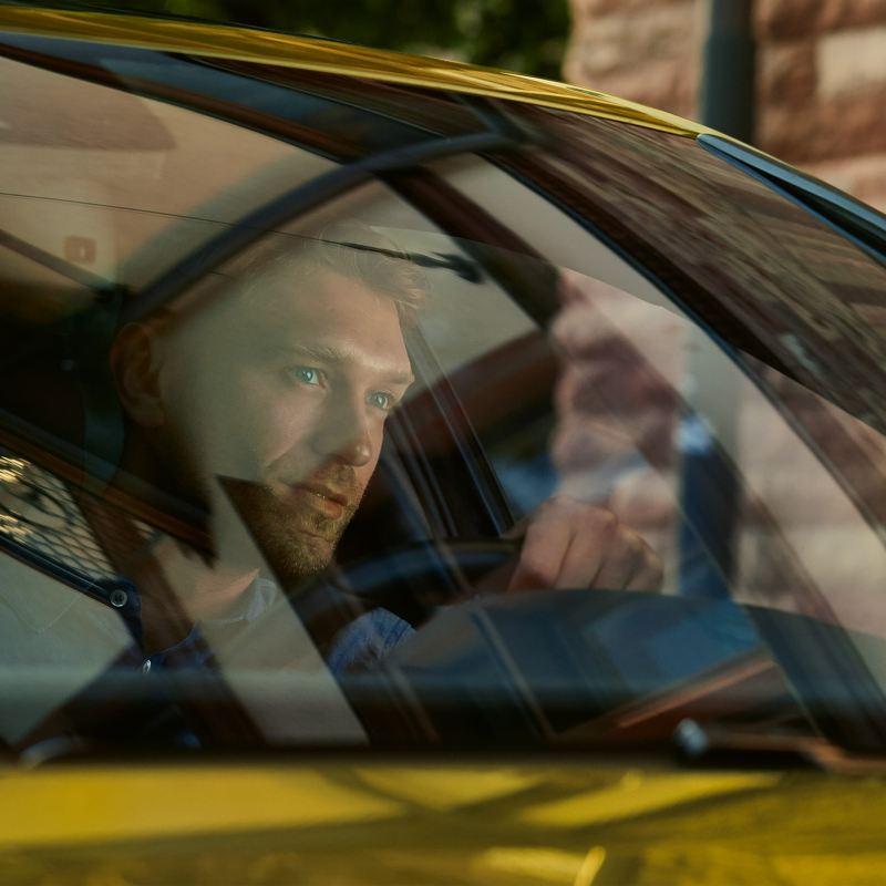Um homem ao volante de uma carrinha Volkswagen.