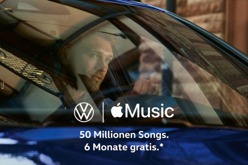 Fahrer im VW Golf schaut aus der Windschutzscheibe, Volkswagen und Apple Logo auf dem Bild