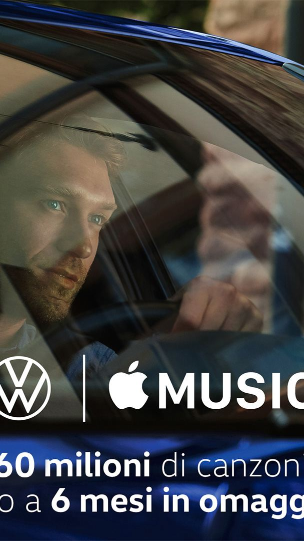 Un uomo al volante di una Volkswagen, fotografato attraverso il parabrezza.