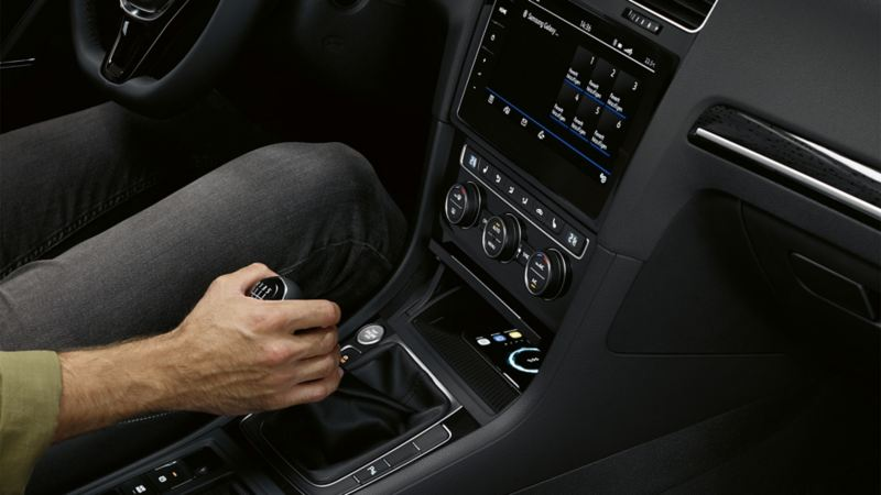 Interior of the VW Golf with the 'Comfort' mobile phone interface, a man's hand on the gear lever