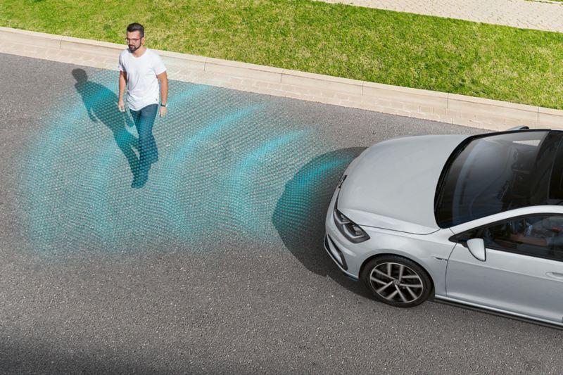 Un pedone attraversa la strada davanti a una VW Golf. Il funzionamento dei sensori del riconoscimento dei pedoni è rappresentato da alcune linee