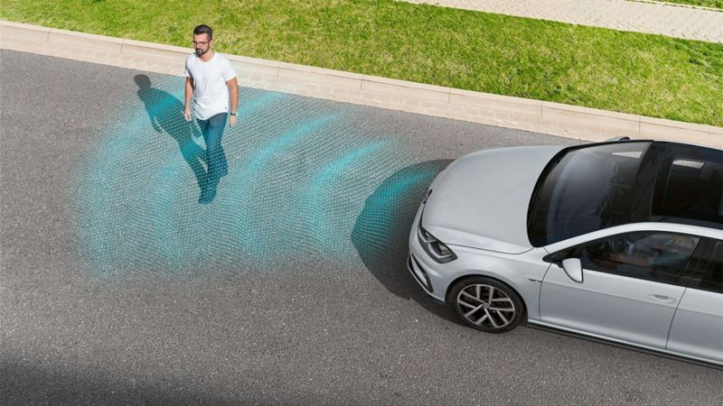 A pedestrian crossing the road in front of a VW Golf. The Pedestrian Monitoring sensor system is depicted using lines