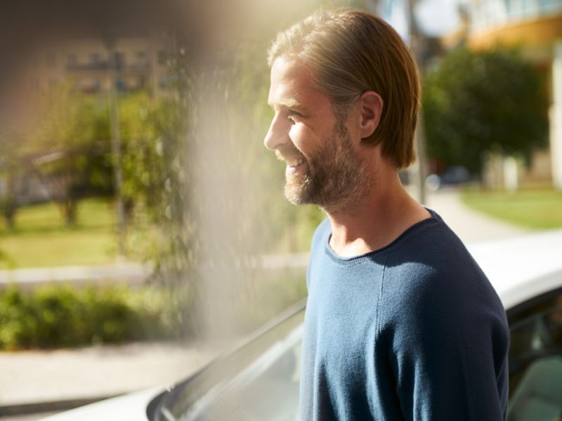 man smiling and standing at a window,windshield of the VW e-Golf  in the background