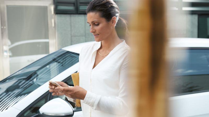 Donna con il cellulare di fronte a una e-Golf