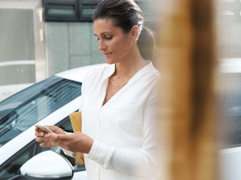 Une femme avec un téléphone portable devant une e-Golf