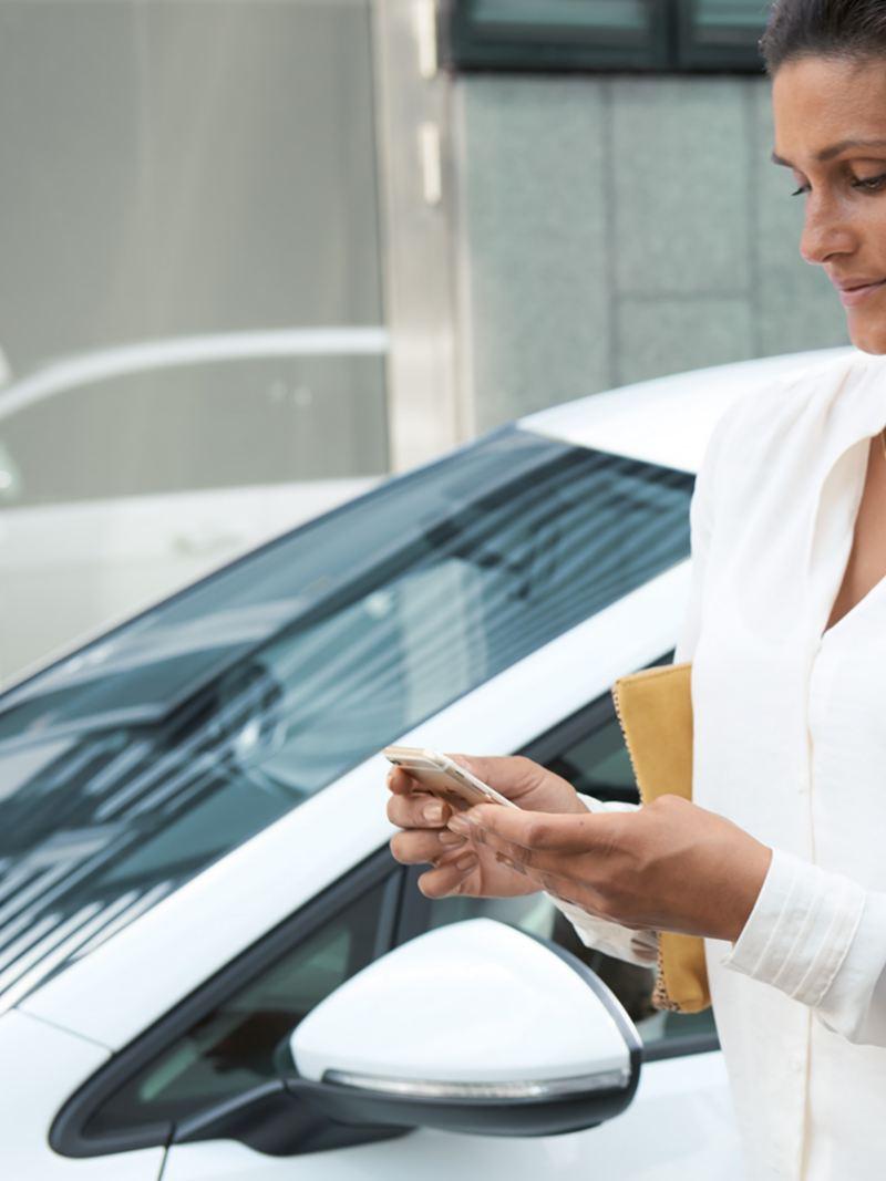 Frau schaut auf ihr Handy, im Hintergrund der VW Golf